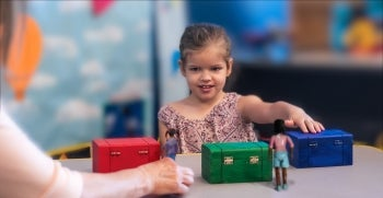 A child decides whether a doll named Maxi will look for his chocolate bar in a red, green or blue box.