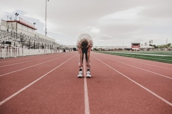 High school student stretching before a track meet.