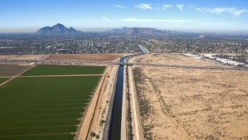 A canal near agricultural fields and infrastructure in the Phoenix metropolitan area