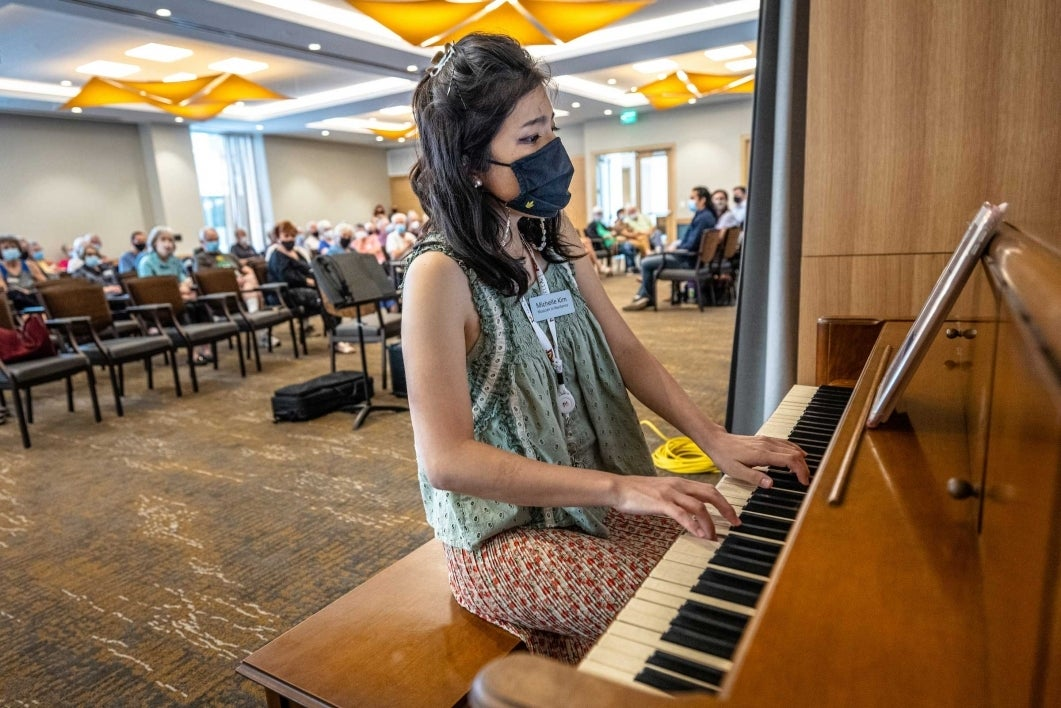 A woman plays the piano in front of a room full of people sitting in chairs