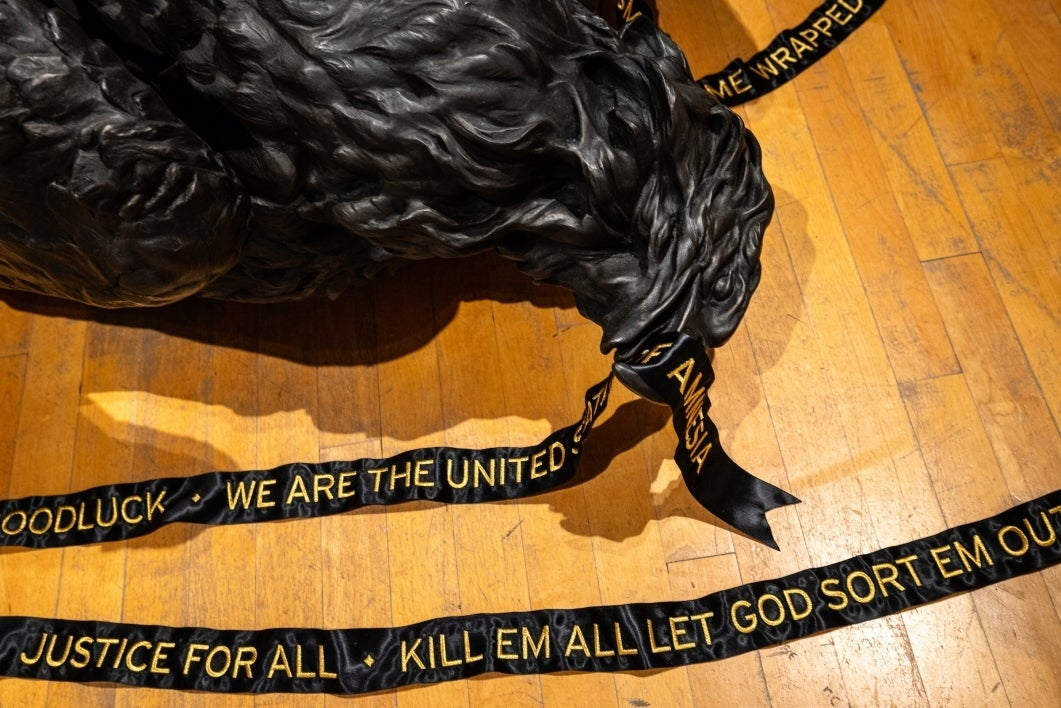 art installation of dead black bird with ribbon in mouth