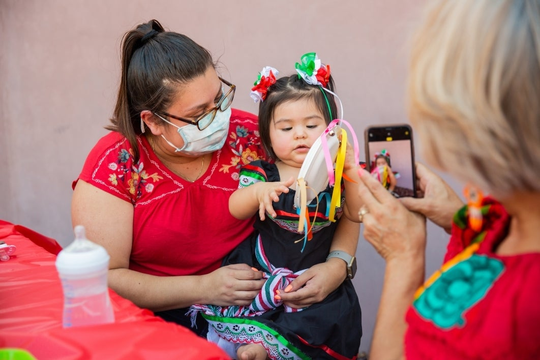 A woman holds a toddler making a Mexican Independence Day paper craft