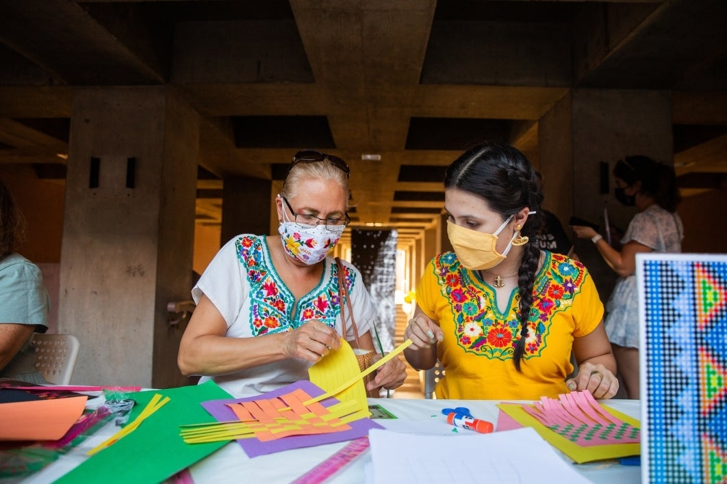 Two women wearing blouses with Mexican embroider sit at a table and work on paper weavings