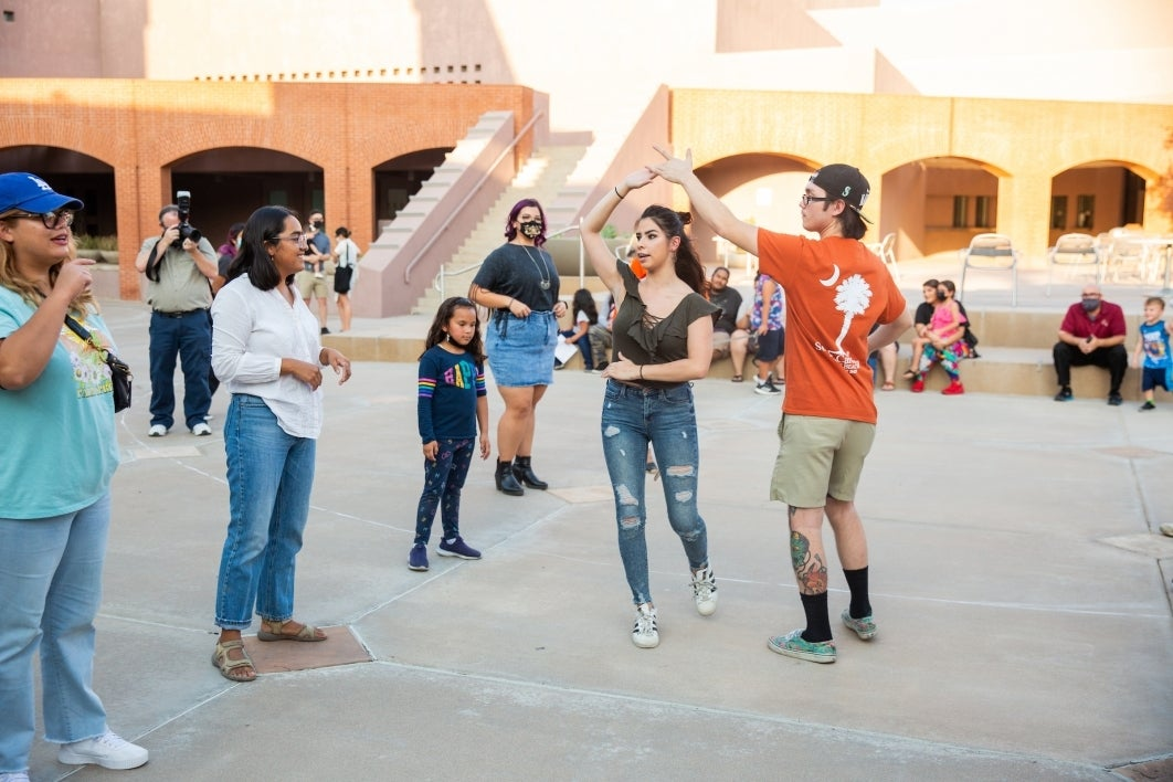 People dance in a courtyard