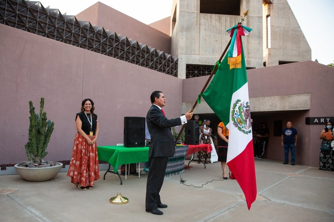 A dignitary holds the Mexico flag and sings the national anthem in a courtyard.