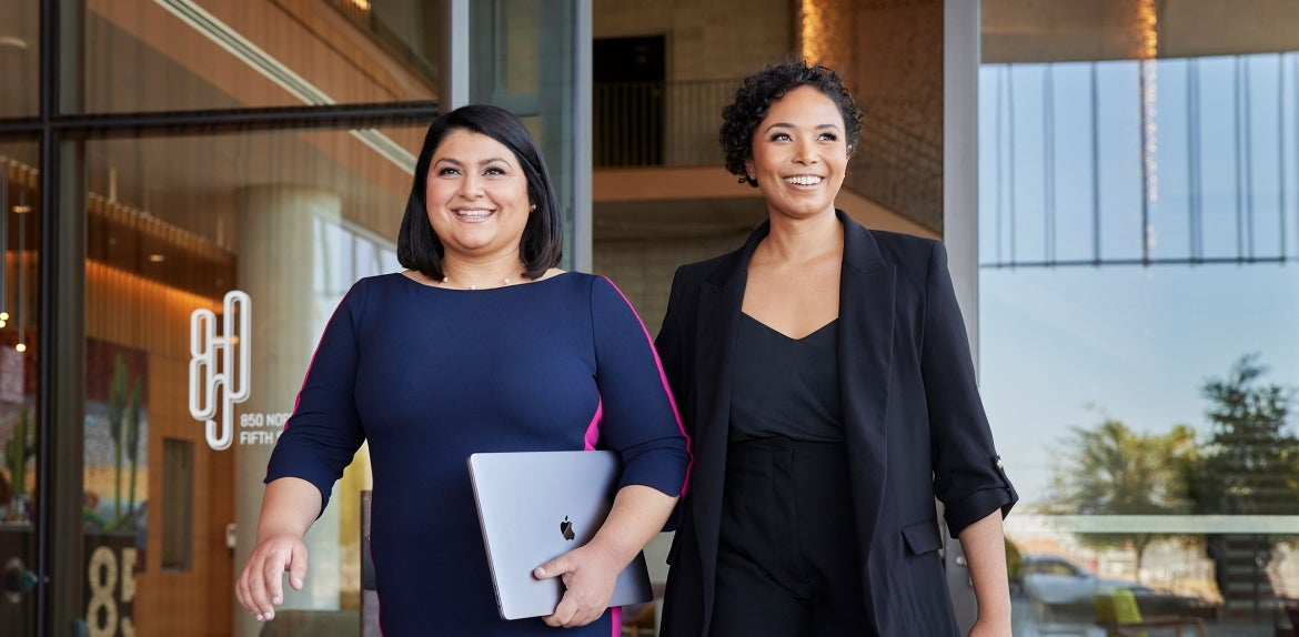 Two women in business attire walk out of a building