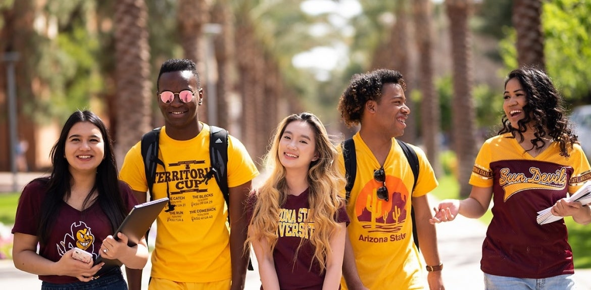 Arizona State University students smiling and walking in a group on campus