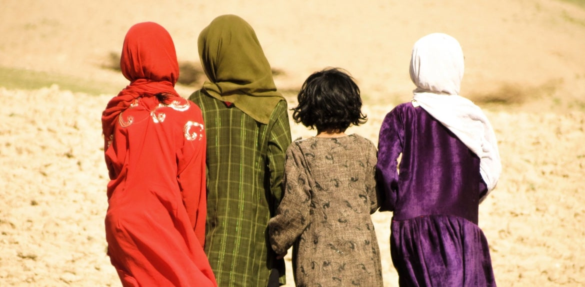 Four Afghanistan girls walking in the mountains, facing away from the camera.