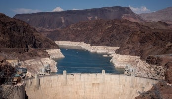 An aerial photo of Lake Mead behind Hoover Dam showing white sections where the water level has drastically receded