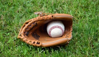 baseball mitt lying on the grass with a ball inside of it