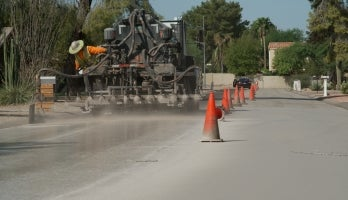 A truck drives down a neighborhood street spraying a light colored treatment to the pavement
