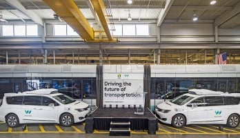 A small stage surrounded by Waymo autonomous cars and Valley Metro light rail train carriages