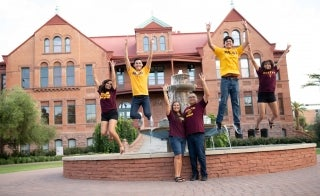 A family of five in maroon and gold celebrates in front of the Old Main fountain
