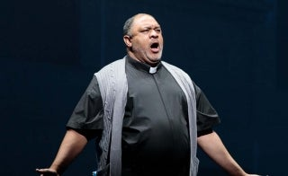 man dressed as a reverend, singing on stage
