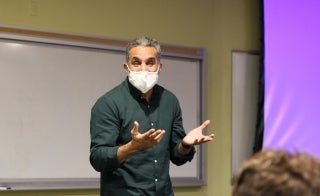 Man wearing a face covering standing at the front of a classroom.