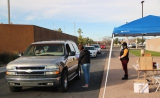 Two masked ASU employees help a line of cars at the Mesa Convention Center check in for FAFSA help
