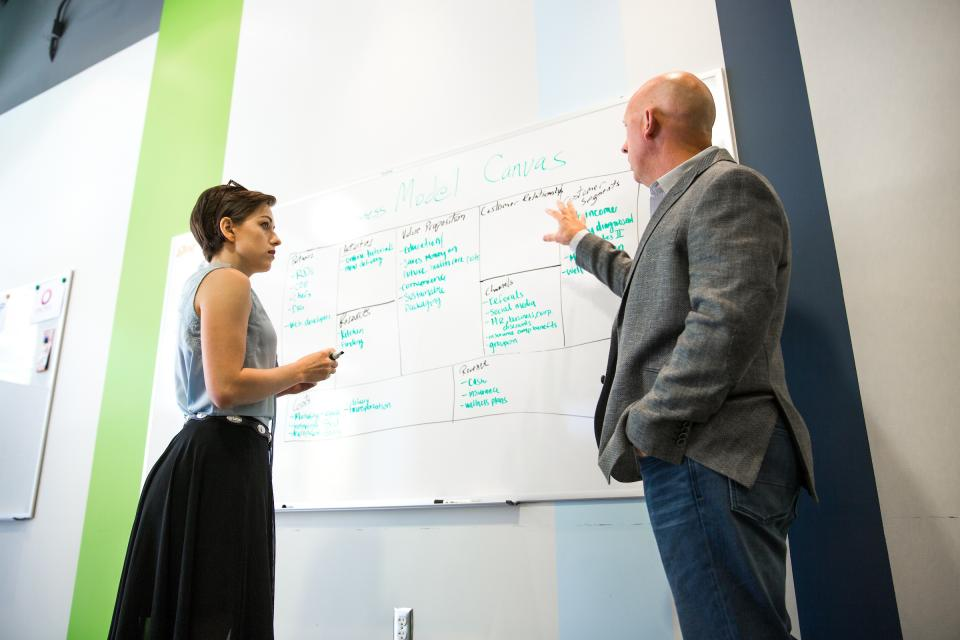 man talking and pointing to notes on a whiteboard while a woman listens