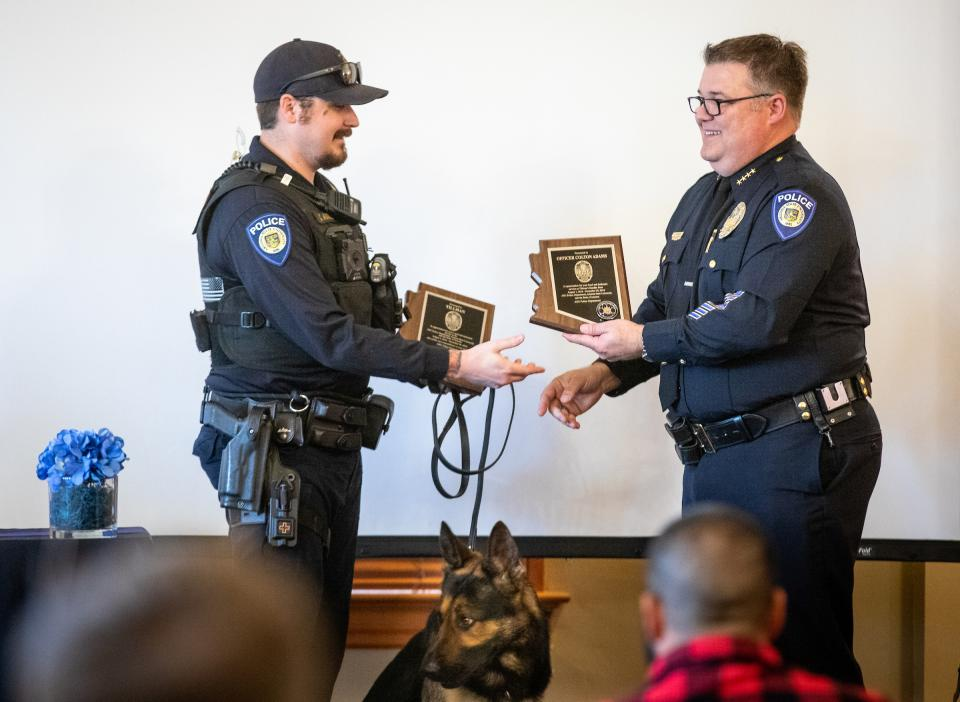 two policemen shaking hands, holding plaques on a stage with a police dog sitting in between them