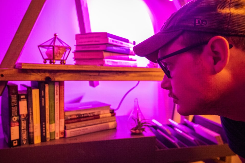 man reading the titles of a stack of books