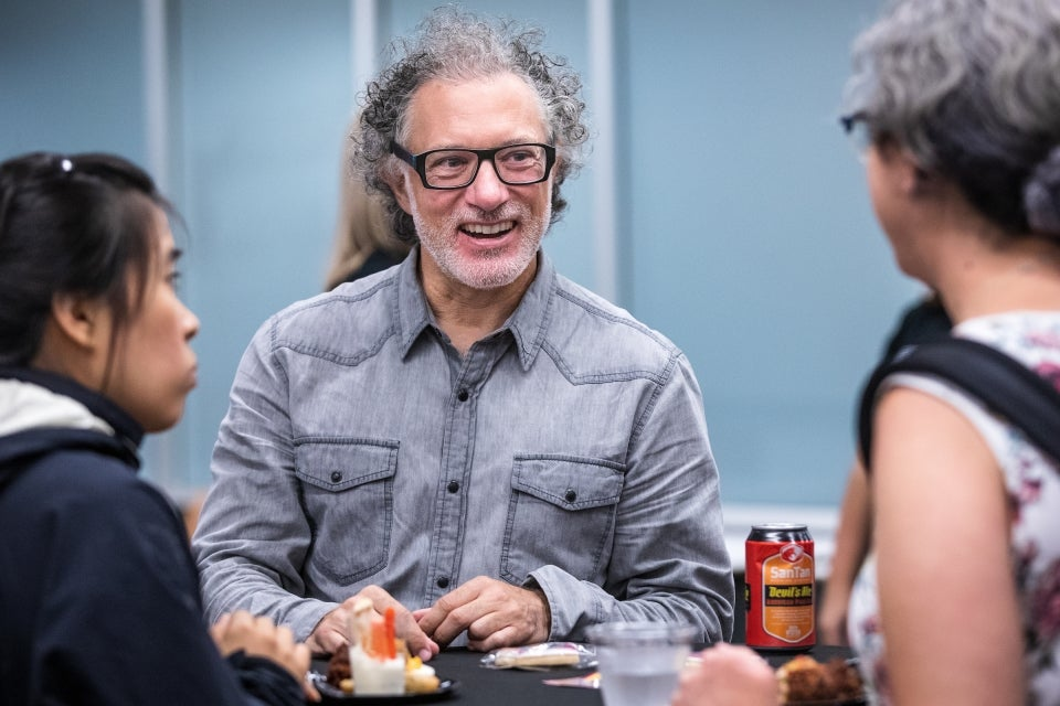 man smiling and talking to people at a cocktail party