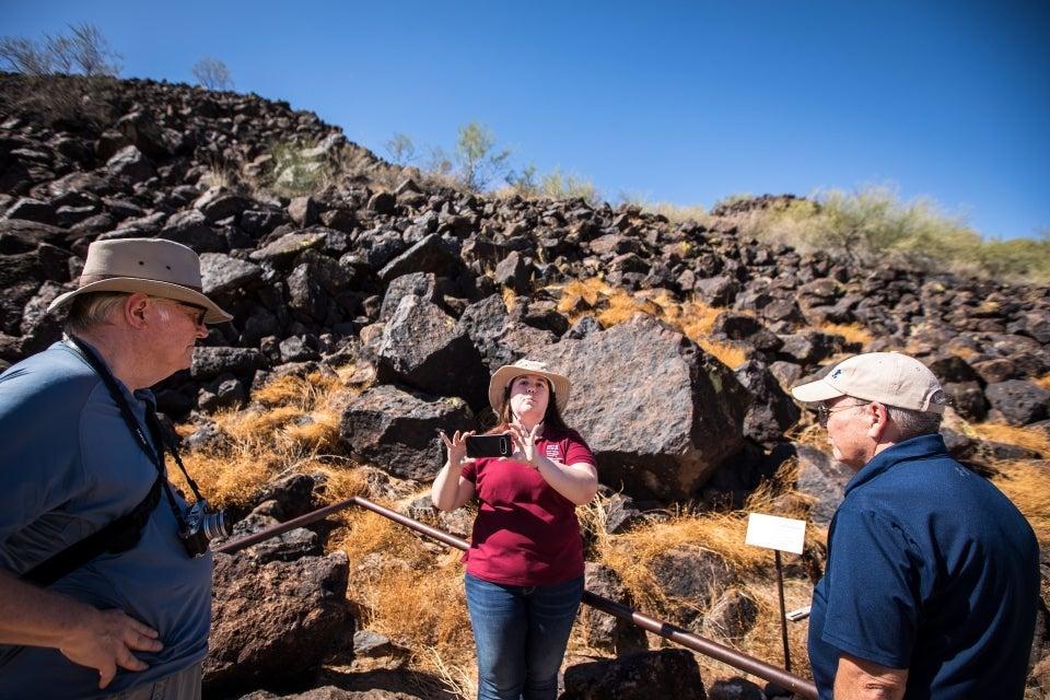 woman taking photo with cell phone at petroglyph reserve