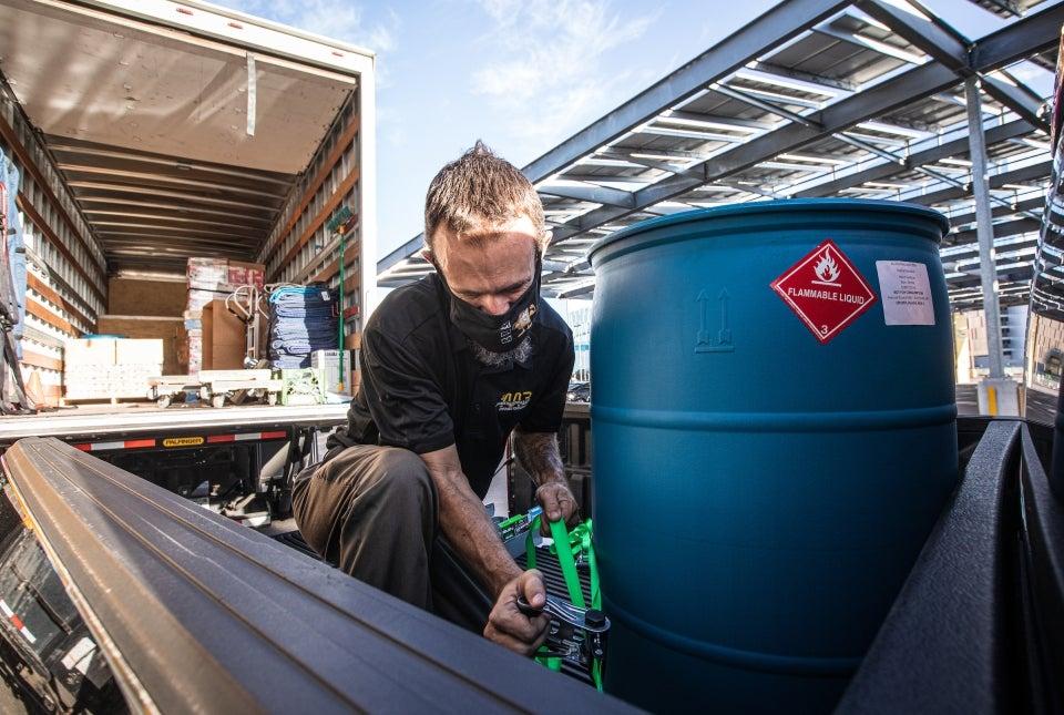 Worker loads a vat of hand sanitizer onto a truck