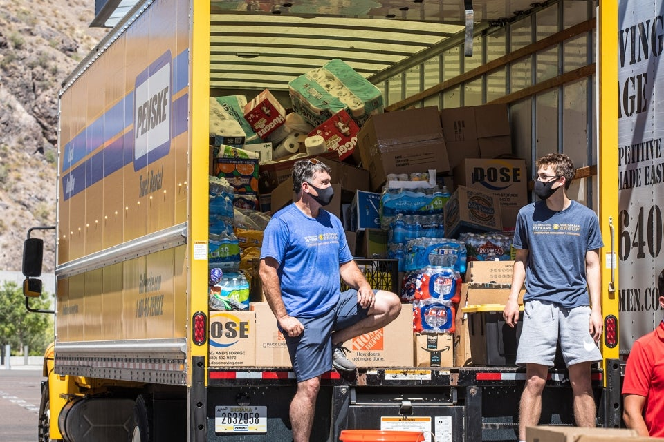 father and stepson talk in front of loaded donation truck