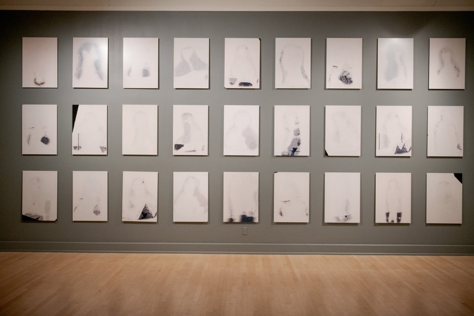exhibit of many rectangular drawing lined up on a wall