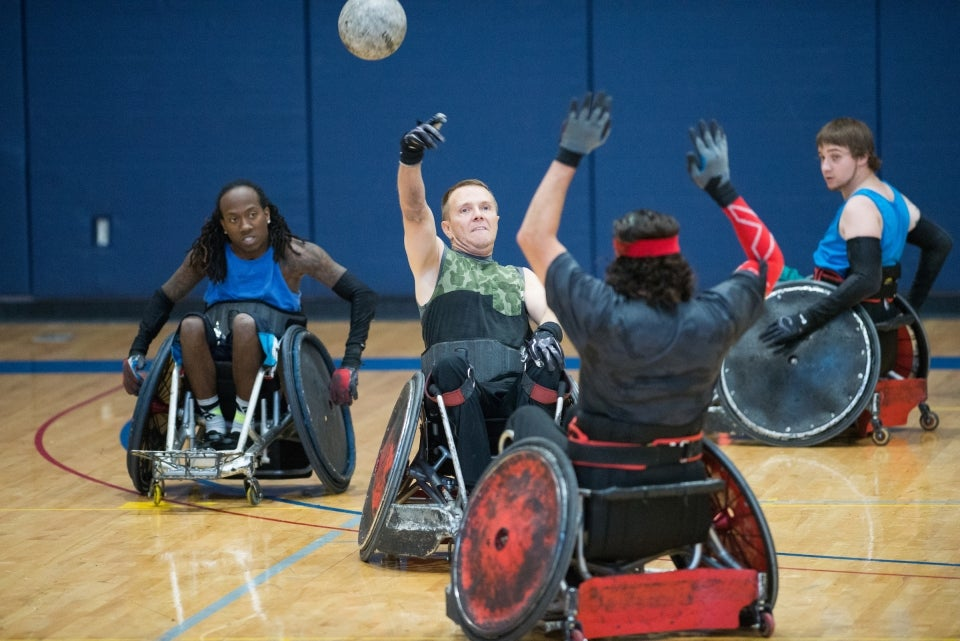 men using wheelchairs while playing rugby