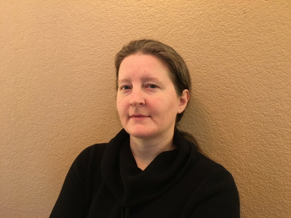 Britta Ager stands in front of a light-colored background. She is looking directly at the camera with a neutral expression. She is wearing a black top and has brown hair that is pulled back behind her ears.