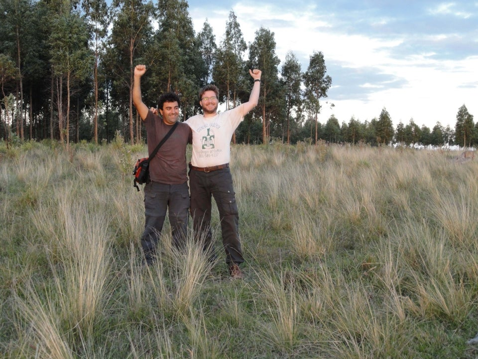 two men in a field raising their arms in the air