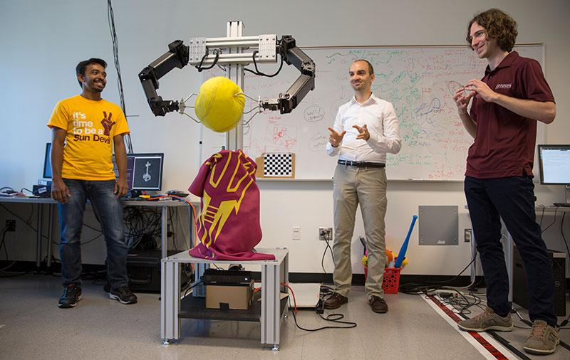 "Three men in a lab crowd around a robot clutching a ball. The caption reads: ""I'm always having a blast with my students, coming up with crazy ideas,"" says Heni Ben Amor (center), shown here with Yash Rathore (left) and Kevin Luck."