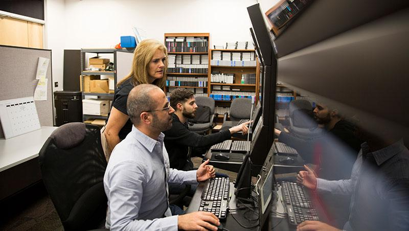 Three people, in a lab, peer at a row of monitors. The caption reads: Nancy Cooke works with Aaron Bradbury (left) and Mustafa Demir on the Synthetic Teammate project. Photo courtesy of the Ira A. Fulton Schools of Engineering.