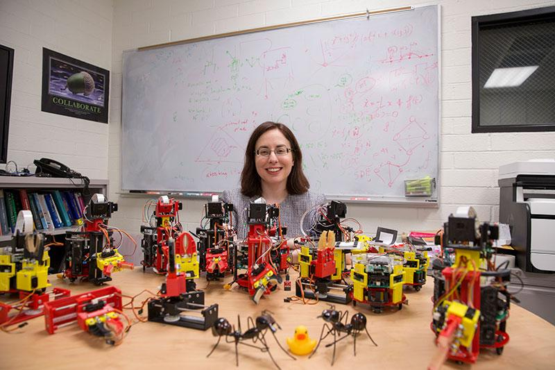 A woman smiles, surrounded by small robots.