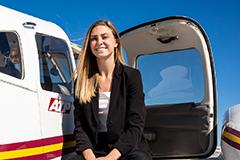 woman sitting next to small plane