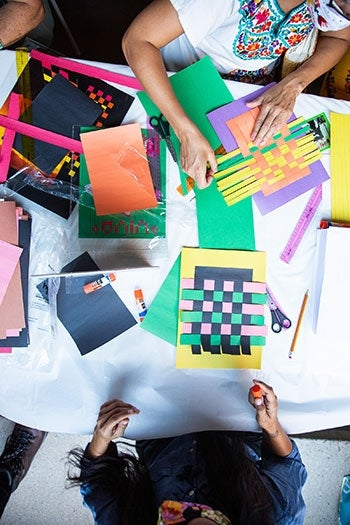 Overhead shot of people working at a table with paper weavings