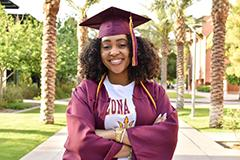 woman in cap and gown posing on Palm Walk