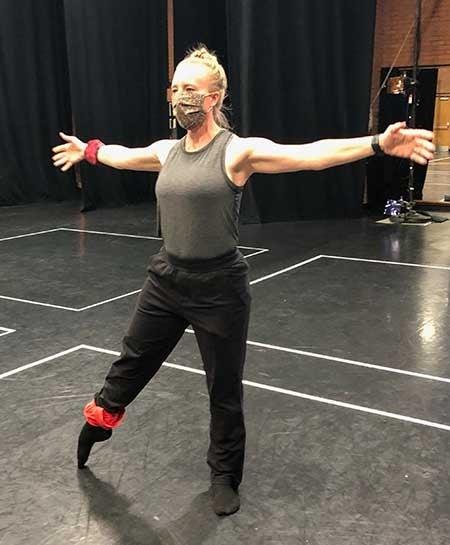 A woman dances in a studio wearing a mask