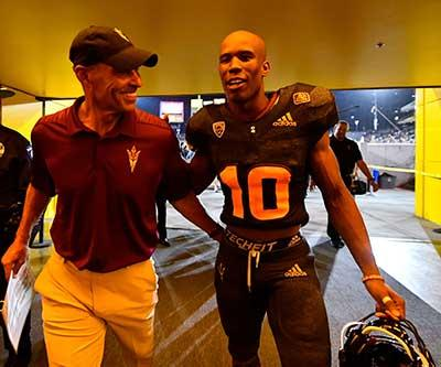 ASU football Coach Herm Edwards and a player walk through the Tillman Tunnel