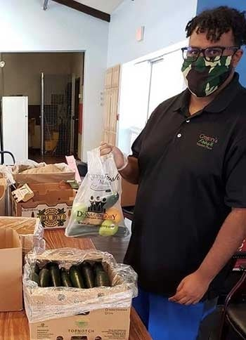 A man packs boxes of produce for vets and low income adults