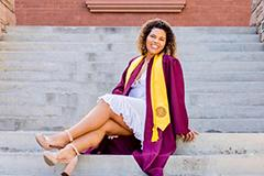 woman posing in graduation gown on Old Main steps