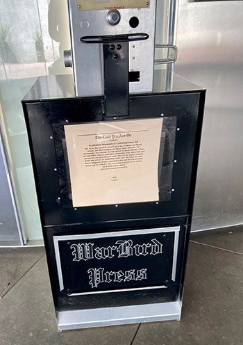 A newspaper vending machine holds printed material with a land acknowledgement