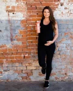 A woman stands against a brick wall, holding a bottle of juice