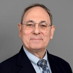 Geoffrey Gonsher wearing dark blue suit, with bluch graphic tie and glasses)