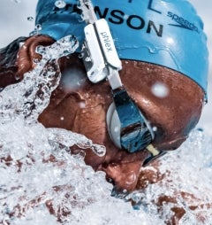 A swimmer swims wearing a cap and a device attached to their goggles